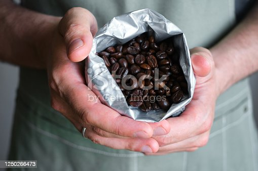 istock Beautiful coffee beans in the hands of a barista. Ready to brew roasted coffee. A man in a culinary apron. Fresh organic coffee. Enjoy the aroma. Making coffee, professional service 1250266473