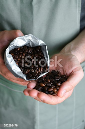 istock Beautiful coffee beans in the hands of a barista. Ready to brew roasted coffee. A man in a culinary apron. Fresh organic coffee. Enjoy the aroma. Making coffee, professional service 1250266476