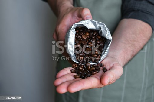 istock Beautiful coffee beans in the hands of a barista. Ready to brew roasted coffee. A man in a culinary apron. Fresh organic coffee. Enjoy the aroma. Making coffee, professional service 1250266546
