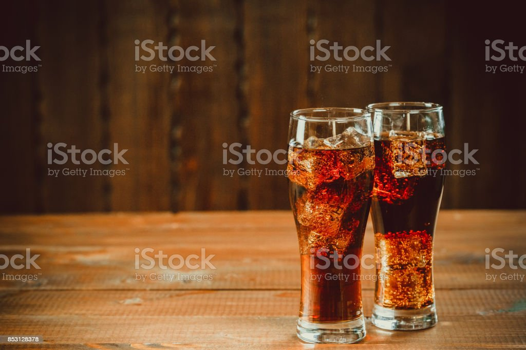 Beautiful cold fizzy cola soda with cubes ice in glasses goblet on old wooden background with free space. Shallow DOF. royalty-free stock photo