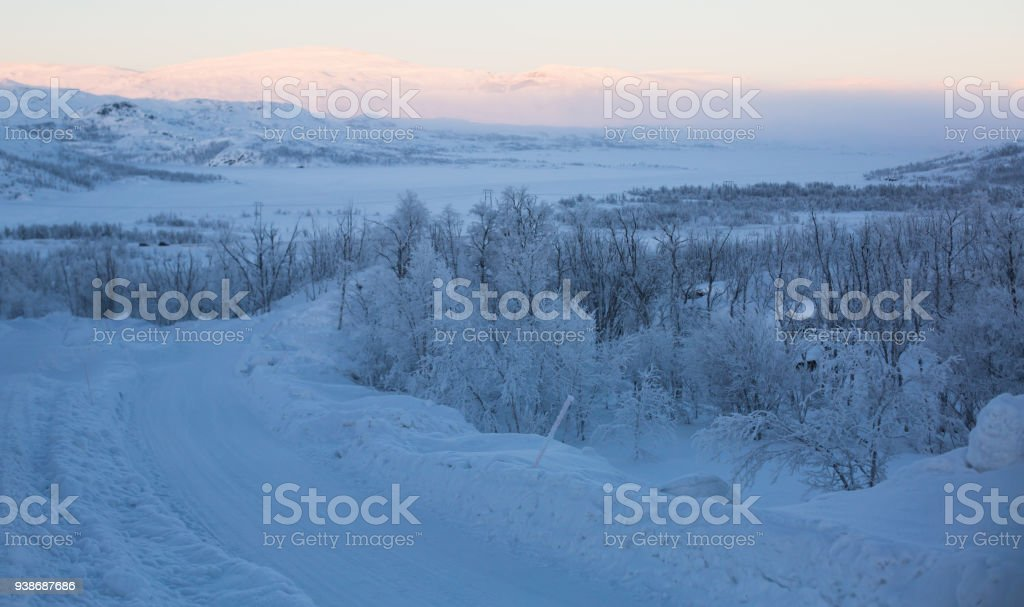 Beautiful cold mountain view of ski resort in Lapland, sunny winter day with slope, piste and ski lift stock photo