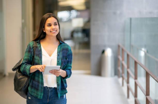schöne college student walkign in richtung klasse halten ihr tablet auf der suche nach tagträumen - öffentliches gebäude stock-fotos und bilder