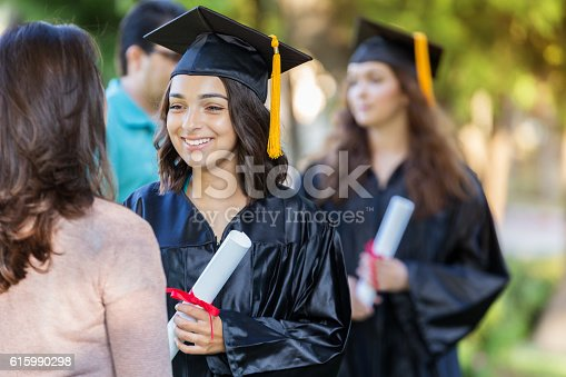 istock Beautiful collegegirl talks with friend after graduation 615990298