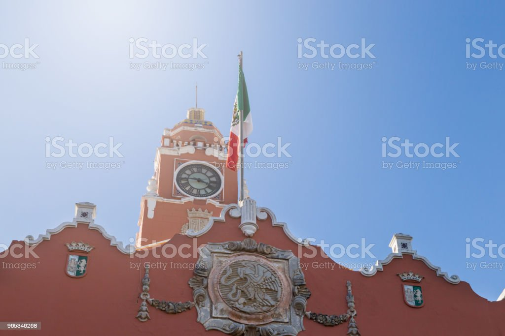 Beautiful colonial city of Merida. Red brick building tower with golden dome and clock in the City center of Merida. Mexican flag flutters on air. zbiór zdjęć royalty-free