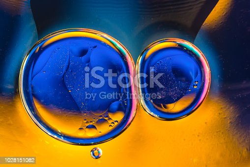 istock Beautiful color abstract background from mixied water and oil. Blue and orange water ripples and bubbles reflections. 1028151082