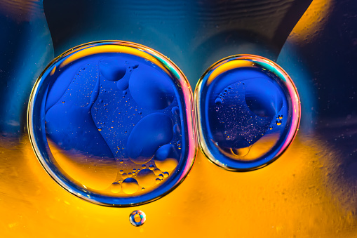 Beautiful color abstract background from mixied water and oil. Blue and orange water ripples and bubbles reflections