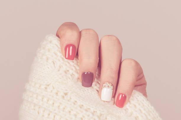 schöne farbige pastell-farben nagellack auf hand, nahaufnahme. nagel-kunst-maniküre-konzept - herbst nagellack stock-fotos und bilder