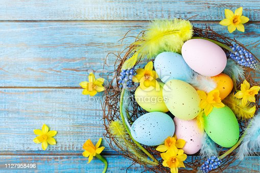 istock Beautiful colorful Easter eggs in nest, feather and spring flowers on rustic table top view. Holiday card or banner. 1127958496