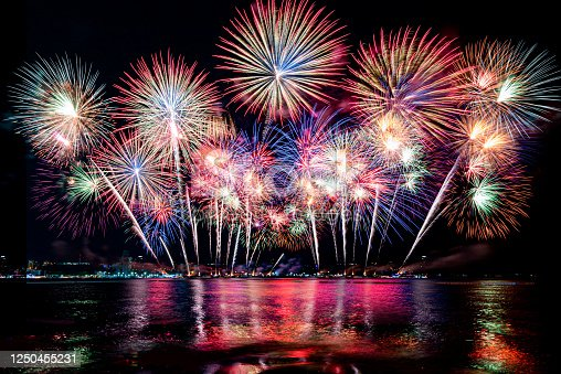 Beautiful colorful firework display over sea on celebration night. Firework festival showing on independence day or happy new year.