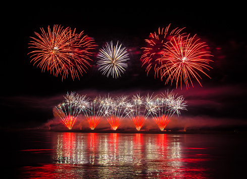 Beautiful colorful holiday fireworks with reflections in the water on the black sky background, close-up, long exposure