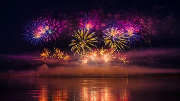 Feux d'artifice de belles vacances coloré avec des reflets dans l'eau sur fond de ciel noir, gros plan, longue exposition - Photo
