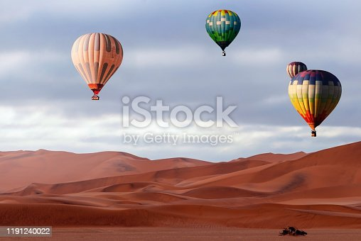 530709531 istock photo Beautiful Colorful Hot Air Baloons and dramatic clouds over the sand dunes in the Namib desert 1191240022
