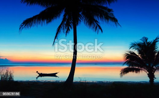 Beautiful colorful sunset with a silhouette of sailing boat and coconut palm