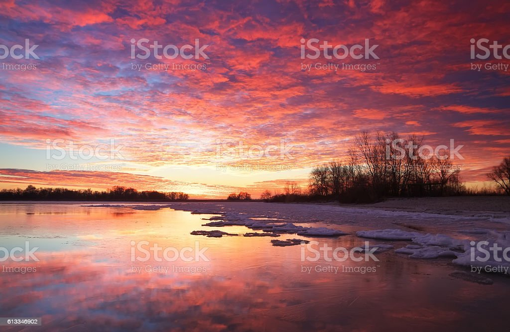 Beautiful colorful winter landscape with frozen lake and sunset stock photo
