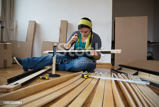 459373065 istock photo Beautiful competent women assembling flat pack furniture - Image 1095305984