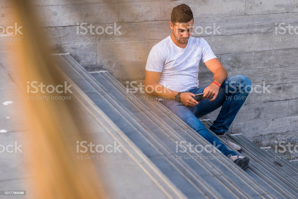 beautiful concentrated caucasian young man use phone and internet to check social media and messaging to friends. new millennial generation concept. city daily life for 18 years old male – zdjęcie