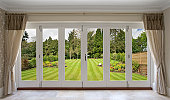 a set of concertina patio doors with silk curtains on either side and a view of a fabulous garden. A large nicely mowed lawn stretches away towards a backdrop of mixed trees.