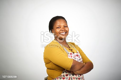 istock Beautiful confident African entrepreneur woman with apron arms crossed cut out 1071305258