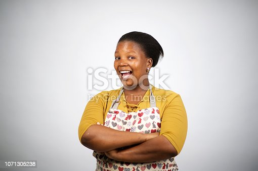 istock Beautiful confident African woman with apron arms crossed cut out laughing 1071305238