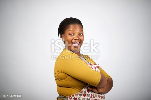 istock Beautiful confident African woman with apron arms crossed cut out side view 1071305260