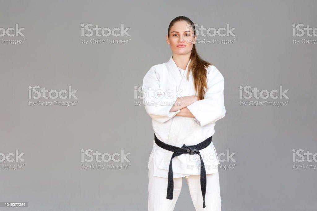 Schöne zuversichtlich sportliche junge Frau im weißen Kimono und Black Belt stehend, gekreuzte Händen und Blick in die Kamera. Japanische Kampfkunst-Konzept. – Foto