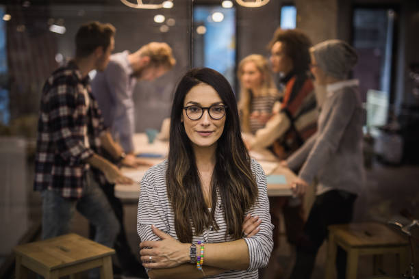 Beautiful confident business leader with crossed arms looking at camera. stock photo
