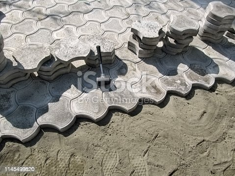 istock Beautiful construction background, the concept of laying paving slabs on a dry sand-cement mix 1145499820