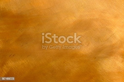 Abstract brushed brown-golden copper or bronze surface, with visible brush strokes. The sheet metal has an appealing cloudy, mottled texture. Horizontal orientation. The image has been shot outdoors during natural day light, full frame and close up. Ideal for backgrounds. The dimensions of the photo are 3300 x 2192 px