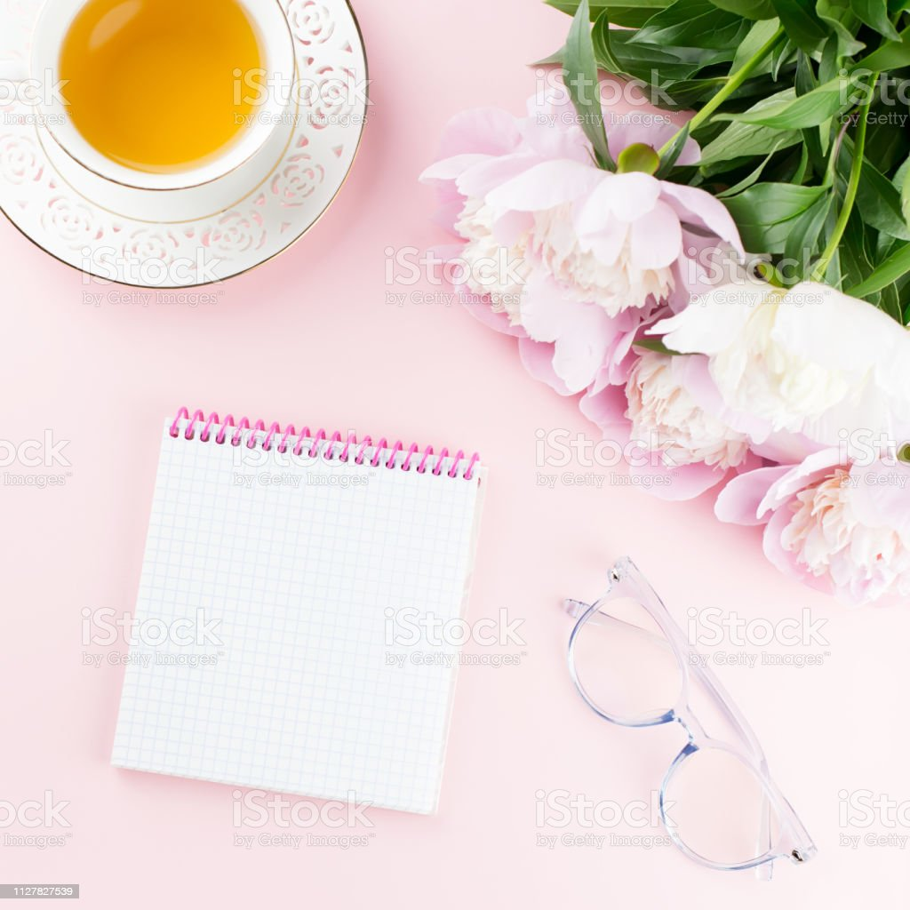 Beautiful cosmetics and flowers flat lay with note book, herbal tea...