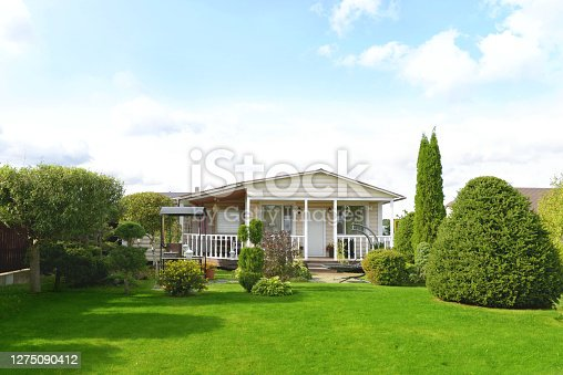 beautiful country house, garden with ornamental trees and plants, flat lawn and landscaping. Garden trees and evergreen conifers