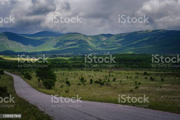 Photo of Beautiful country road before a thunderstorm at sunset.