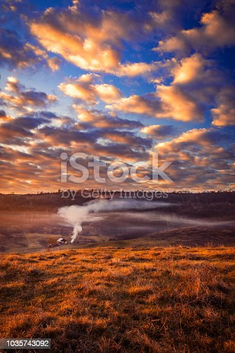 1034754000 istock photo Beautiful countryside scene in the morning with a house and smoke from a fire againt a beautiful sky 1035743092
