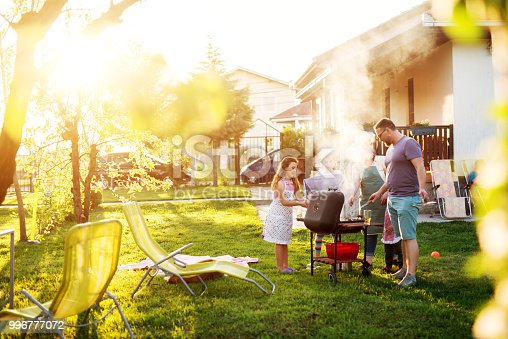 Beautiful couple and their adorable children have gathered around the grill  in front of the house.