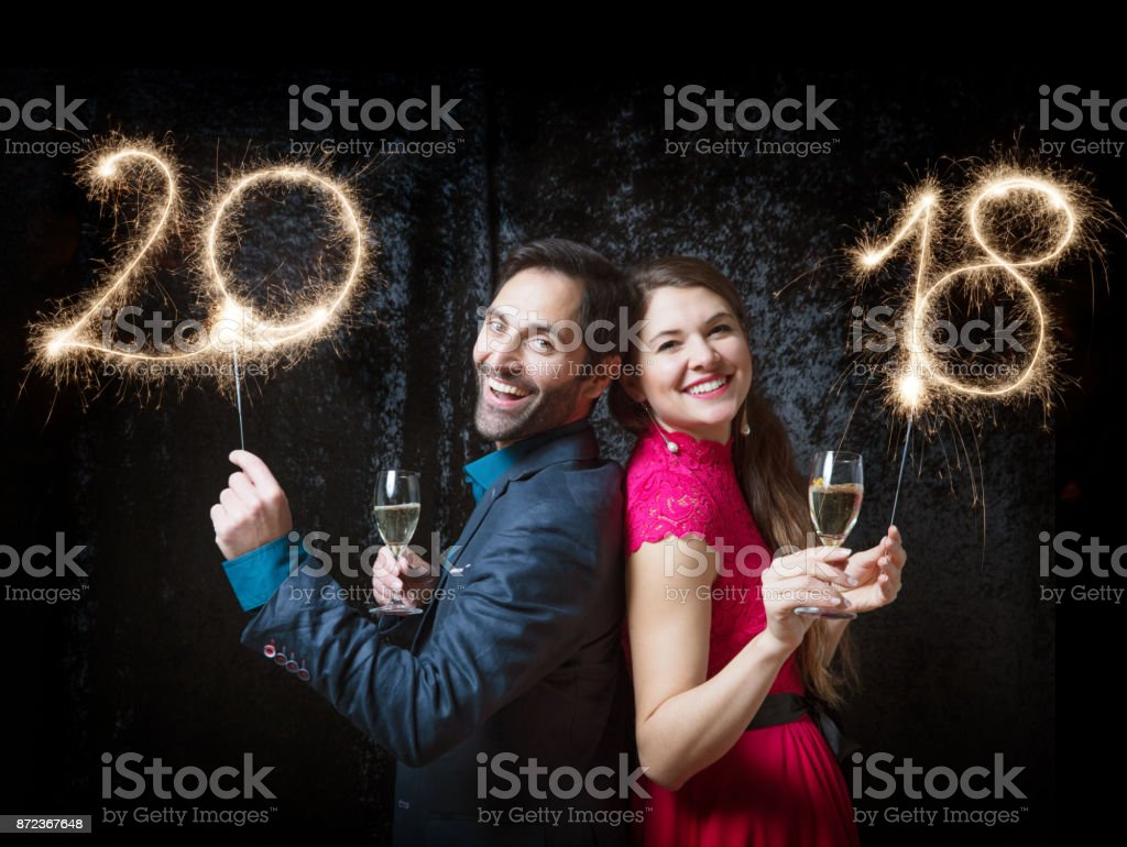 Beautiful couple celebrating New Year\'s Eve with sparkler 2018