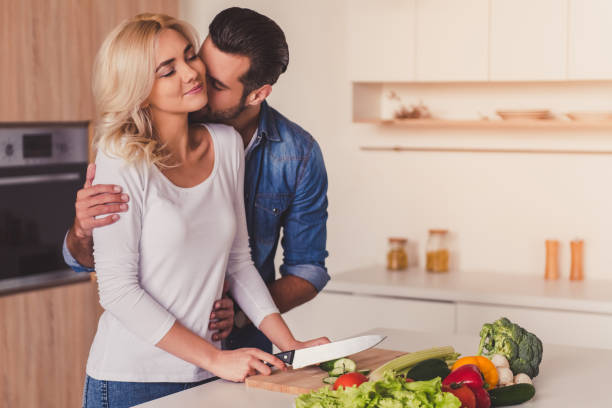 beautiful couple cooking - kissing on neck stock photos and pictures