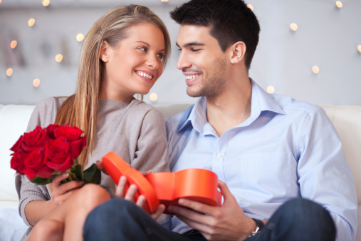 Beautiful couple with roses and gift box embracing and smiling at camera.See more LIFESTYLE images with this YOUNG COUPLE. Click on image below for lightbox.