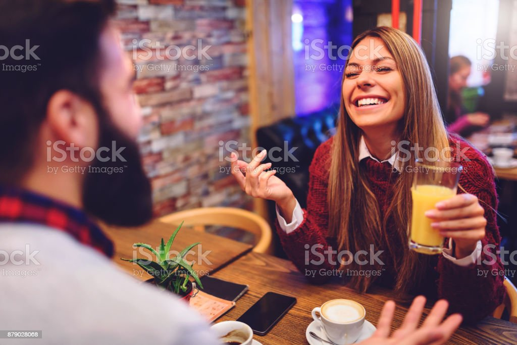 Beautiful couple drinking coffee talking and having fun in cafeteria stock photo
