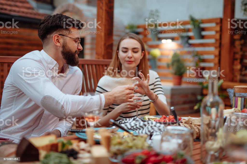 Beautiful couple eating cheese in a summer garden stock photo