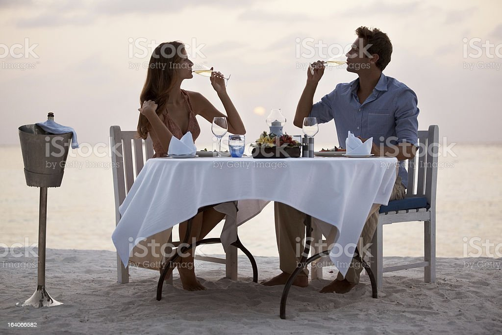 Beautiful couple enjoying a romantic dinner at the beach stock photo