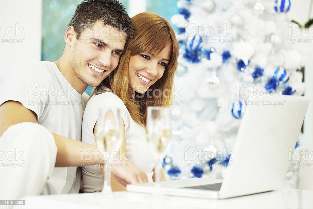 Beautiful couple enjoying at home while using laptop. royalty-free stock photo