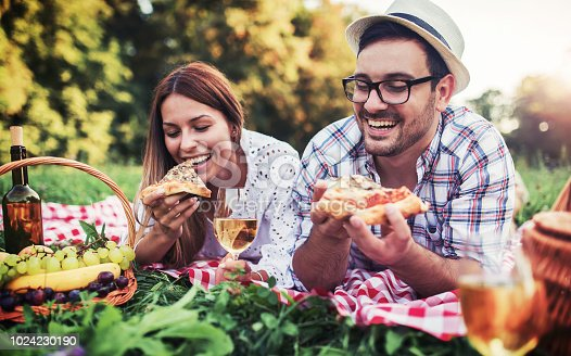 Picnic time. Young couple eating pizza and drinking wine on picnic in the park. Love and tenderness, dating, romance, lifestyle concept