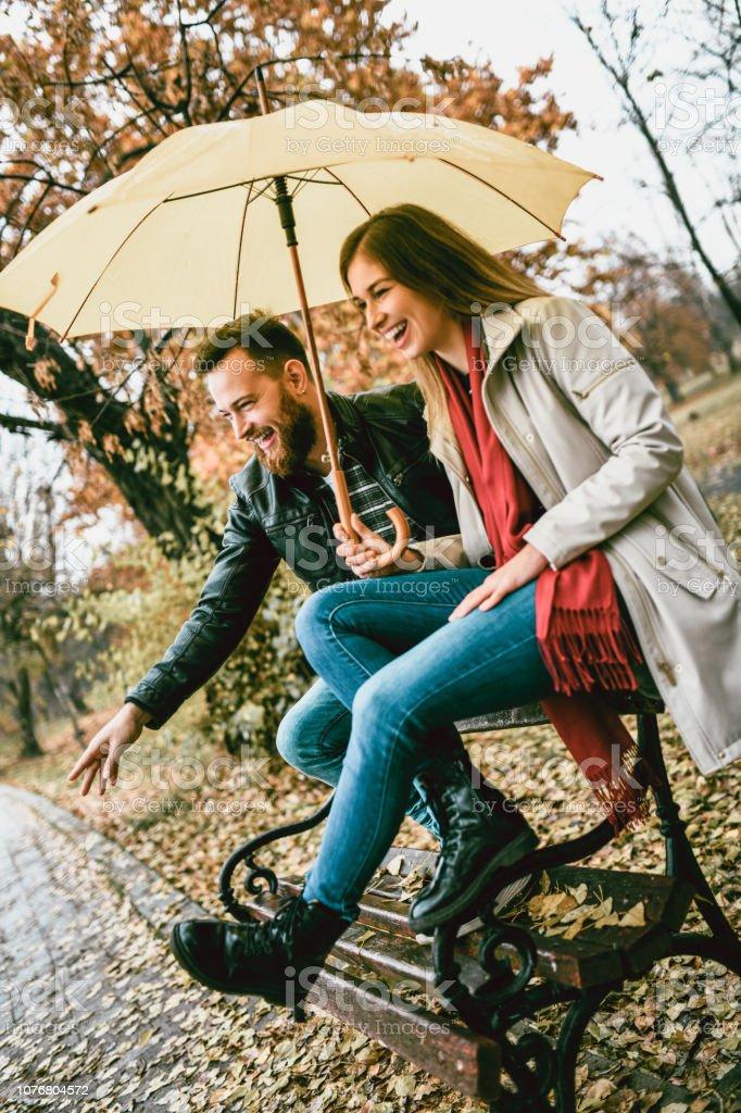 Beautiful Couple Enjoying Rainy Day On Park Bench
