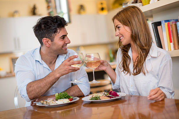 Beautiful couple having dinner Beautiful couple having dinner at home and toasting table for two stock pictures, royalty-free photos & images