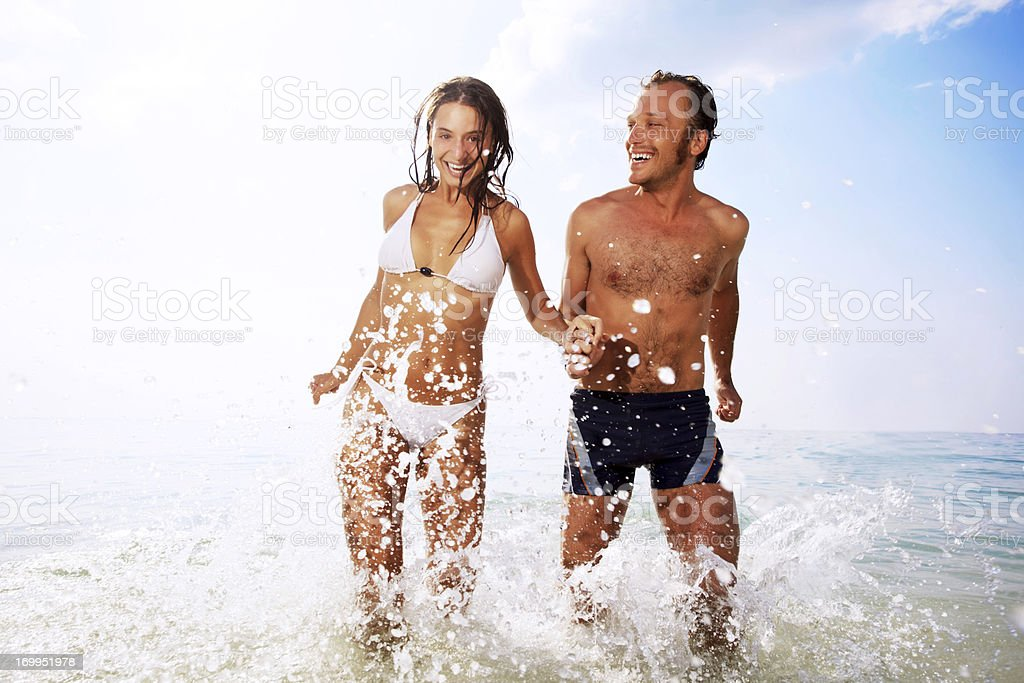 Beautiful couple having fun at the beach. stock photo