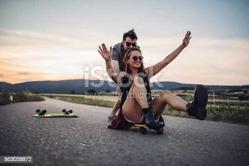 Hipster couple skating on the road