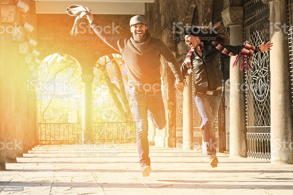 Beautiful couple holding hands and jumping under ancient columns stock photo