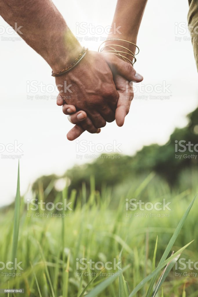 Beautiful couple holding hands on the field stock photo