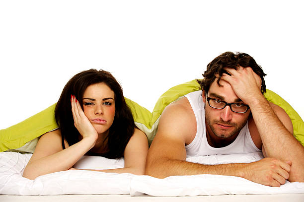 Beautiful couple in bed under a green duvet stock photo