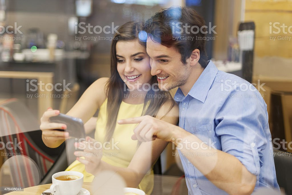 Beautiful couple in cafe with mobile phone royalty-free stock photo