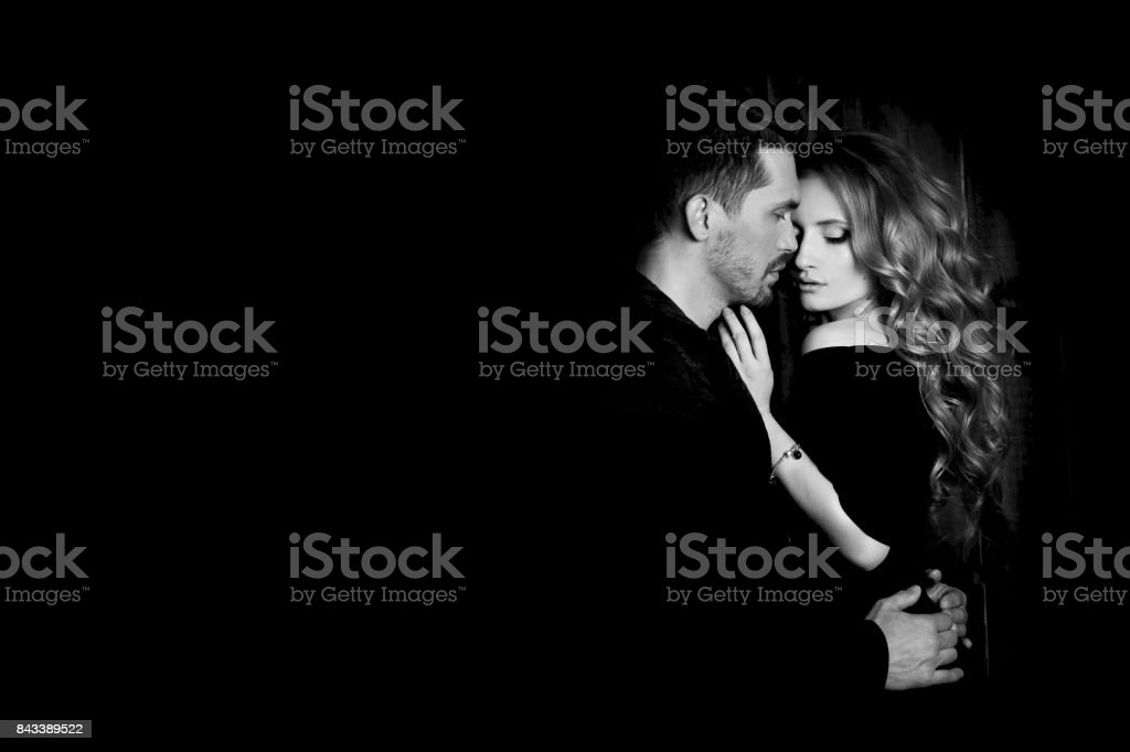 Beautiful couple in love hugging against black background. Studio black and white portrait photo of a girl blondes and a guy with short hair. Valentine's day. Loving married couple. Family happiness stock photo